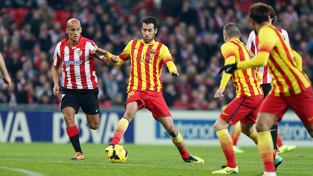 Busquets controls the ball under pressure from Mikel Rico, whilst Iniesta and Neymar look on