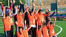 A group of participants in the FutbolNet project in Qatar wave their arms in celebration