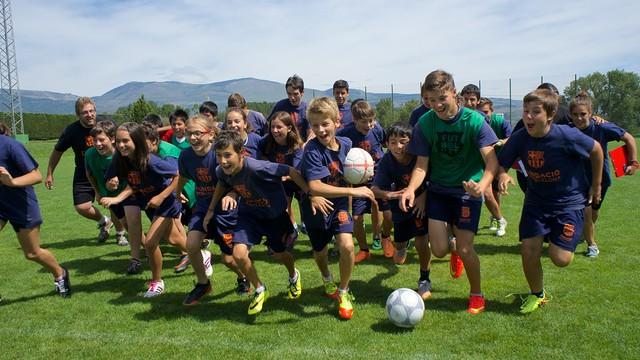 Un grupo de niños corren en estampida sobre un campo de césped.