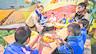 Unas educadoras ofrecen higienizante de manos a un grupo de niños que atiende uno de los talleres de la campaña