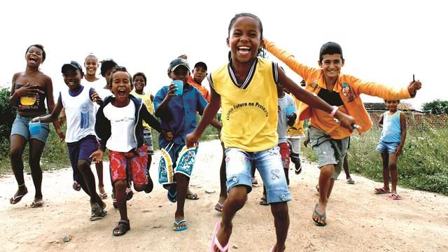 Un grupo de niños corriendo hacia cámara mientras sonríen