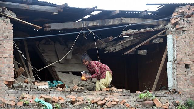 Una dona recull alguns objectes de casa seva, derruïda pel terratrèmol