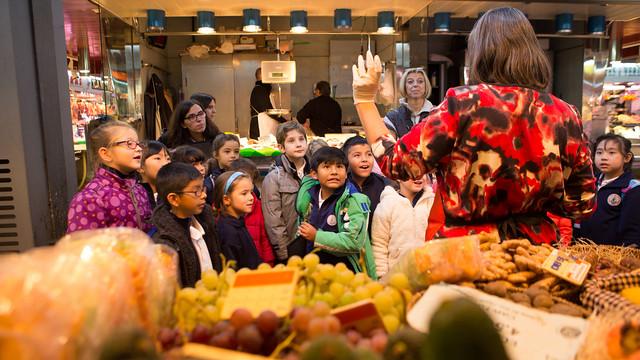 Un grup de nens atén un taller d'alimentació al mercat de la Concepció de Barcelona